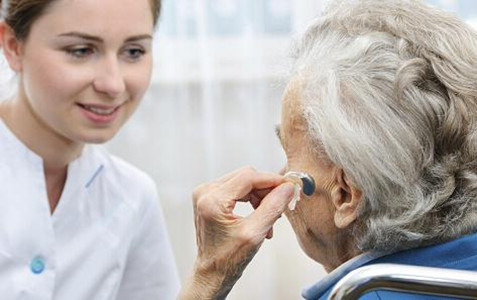 Female doctor helps female patient with hearing aid