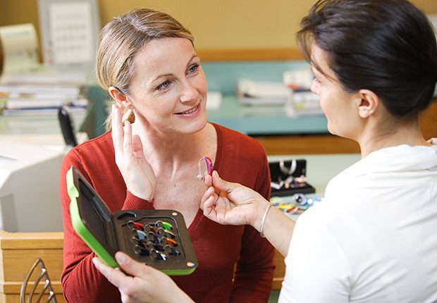 Female Doctor provides female patient with different hearing aid examples