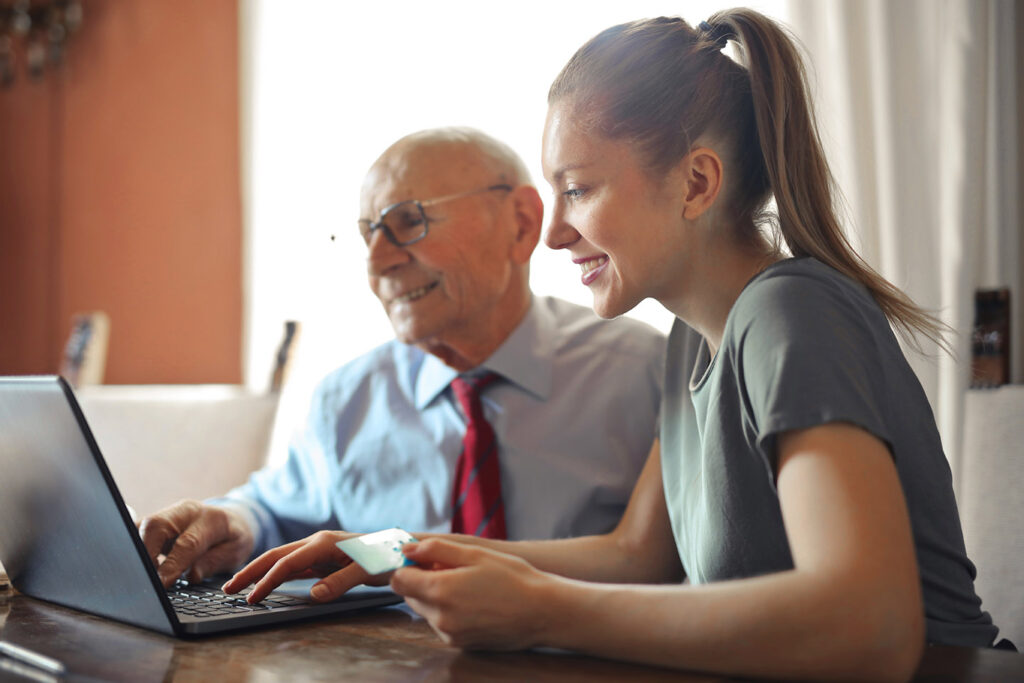 elderly man and young woman use a computer