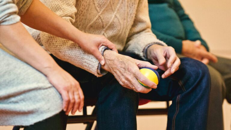 women comfortingly holding arm of an elderly man holding a stress ball